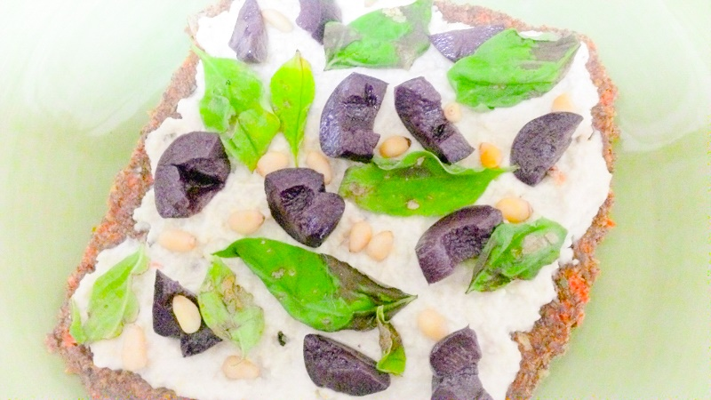 a slice of raw vegan pizza withkalamata olives, fresh basil, and pine nuts