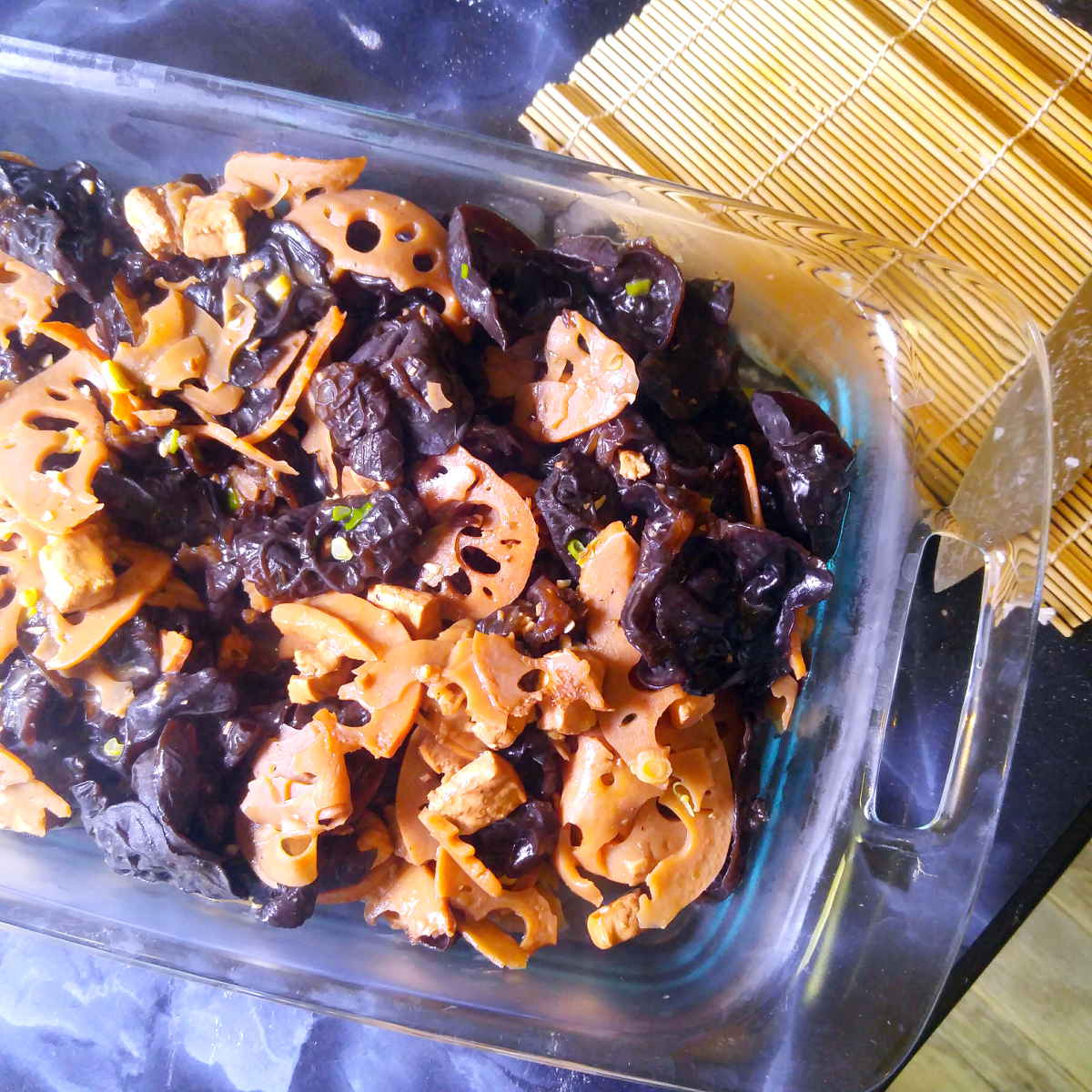 Lotus root wood ear mushroom tofu stir fry in a serving dish
